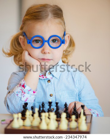 Portrait of beautiful little girl with chess - stock photo