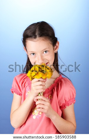 Portrait of beautiful little girl with dandelions on blue background