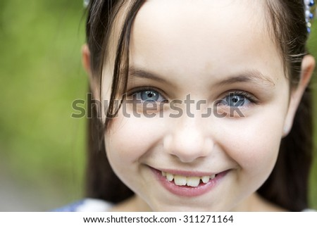 Portrait of beautiful little smiling girl with brunette hair and blue eyes in white blouse looking forward standing sunny day outdoor on natural background closeup, horizontal picture - stock photo