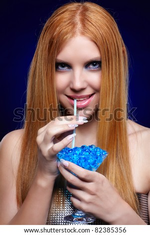 portrait of beautiful long-haired blue-eyed redhead girl drinking fantasy cocktail - stock photo