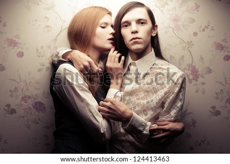 Portrait of beautiful long haired people in vintage style: handsome boy with brown hair and whispering gorgeous red-haired girl posing together. Studio shot.