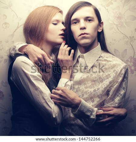 Portrait of beautiful long haired people in vintage style: handsome boy with brown hair and whispering gorgeous red-haired girl posing together. Studio shot