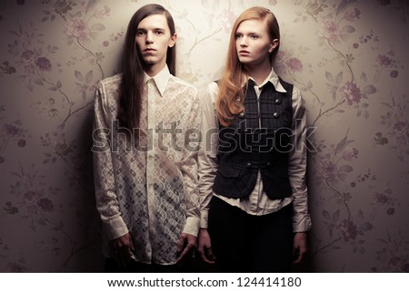 Portrait of beautiful long haired people looking like dolls in vintage style: handsome boy with brown hair and gorgeous red-haired girl posing together. Studio shot. - stock photo
