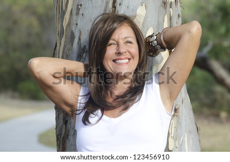 Portrait of beautiful looking middle aged woman leaning relaxed with arms up and happy smile against tree in park, with blurred background. - stock photo