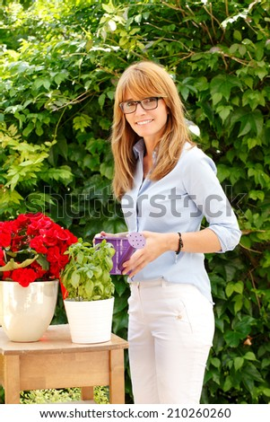 Portrait of beautiful mature florist standing in garden. Small business.  - stock photo