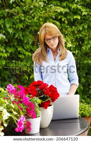 Portrait of beautiful mature florist standing. Small business.  - stock photo