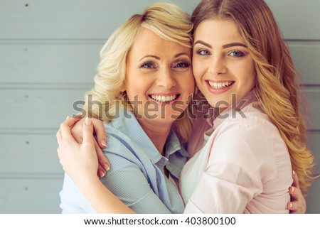 Portrait of beautiful mature mother and her daughter hugging, looking at camera and smiling, against gray background - stock photo