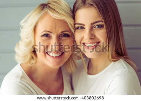 Portrait of beautiful mature mother and her daughter hugging, looking at camera and smiling, against gray background