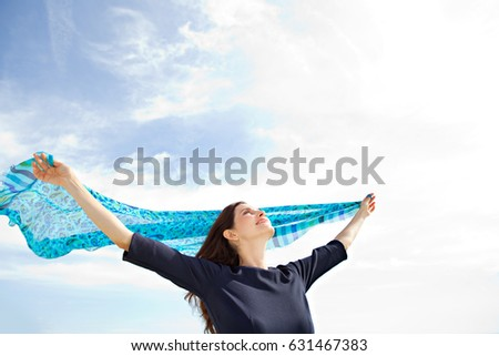 Portrait of beautiful mature woman holding raising silk fabric up against blue sky, floating in the breeze with sunshine, smiling outdoors. Dreamy joyful female enjoying healthy lifestyle, exterior.