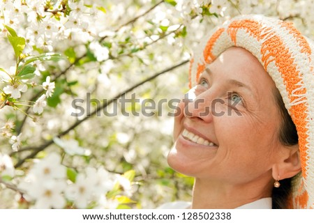 Portrait of   beautiful mature woman in spring garden. - stock photo