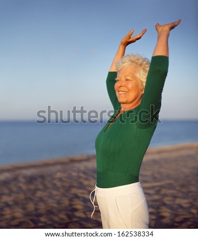 Portrait of beautiful mature woman practicing yoga on beach with copyspace. Old caucasian woman exercising outdoors to stay fit. Health and fitness concept. - stock photo