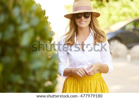 Portrait of beautiful mature woman walking on the street. Happy female wearing straw hat and sunglasses while on summer vacation.