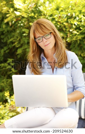 Portrait of beautiful mature woman with laptop sitting in garden and working at home.