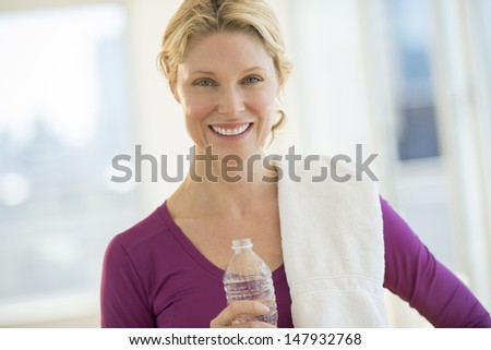 Portrait of beautiful mature woman with water bottle and towel smiling in health club - stock photo