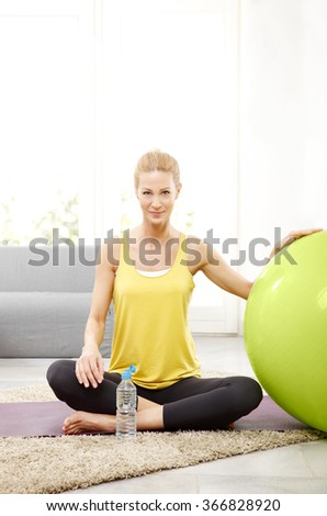 Portrait of beautiful middle age woman drinking a bottle of water while relaxing after fitness workout at home.