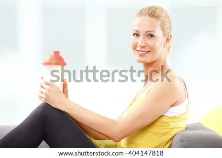 Portrait of beautiful middle age woman holding in her hand a protein shaker while sitting on couch after home workout.  - stock photo