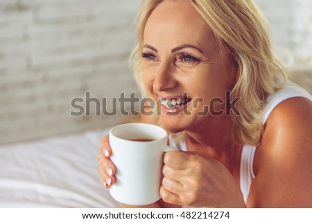 Portrait of beautiful middle aged woman holding a cup of coffee, looking away and smiling