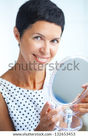Portrait of beautiful middle aged woman looking at cosmetic mirror