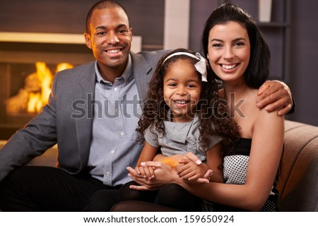 Portrait of beautiful mixed race family at home by fireplace, all smiling, little girl in the middle. - stock photo