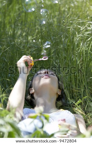 Portrait of beautiful model in the grass blowing soap bubbles
