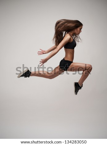 portrait of beautiful modern jumping dancer. studio grey background - stock photo
