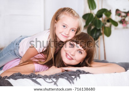 Portrait of beautiful mother and her daughter hugging in a bed, looking at camera. Happy family.