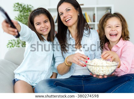 Portrait of beautiful mother and her daughters eating popcorn at home. - stock photo