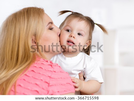 Portrait of beautiful mother kissing her child girl - stock photo