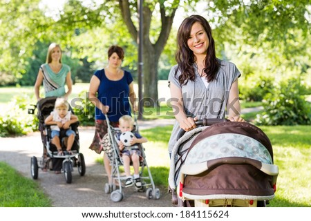 Portrait of beautiful mother pushing baby stroller in park with friends and children in background - stock photo