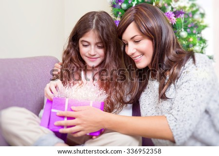 Portrait of beautiful mother with cute daughter with pleasure opening gift box, receiving magical glowing present, wonderful surprise on Christmas eve - stock photo