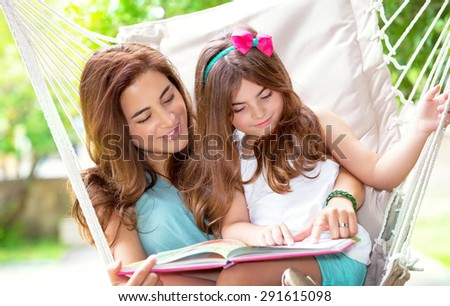 Portrait of beautiful mother with cute little daughter sitting on backyard in hammock and reading interesting book, spending wonderful summer holidays together - stock photo