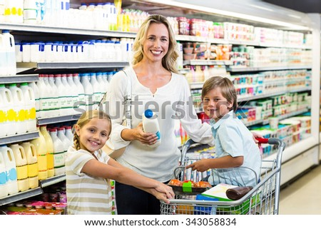 Portrait of beautiful mother with her children at the supermarket - stock photo
