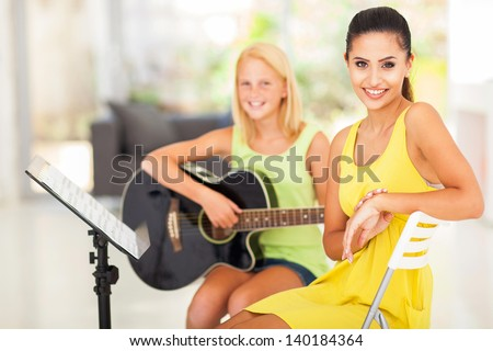 portrait of beautiful music tutor and student - stock photo