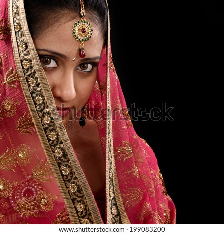 Portrait of beautiful mystery young Indian woman covering her face by headscarf, looking at camera, copy space at side, isolated on black background. - stock photo