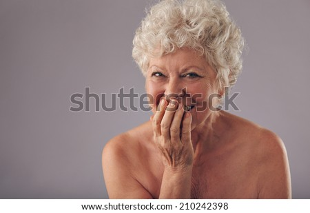 Portrait of beautiful naked senior female smiling at camera against grey background. Old woman smiling with hands on mouth with copy space. - stock photo