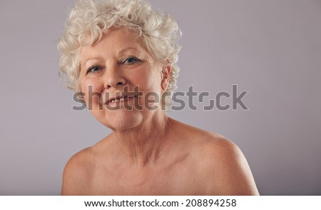Portrait of beautiful naked senior woman looking happy against grey background. Confident old caucasian female with smile on her face. - stock photo