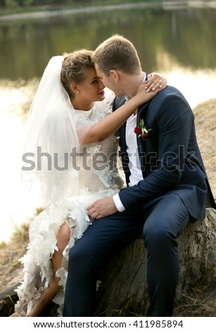 Portrait of beautiful newly married couple sitting at river - stock photo