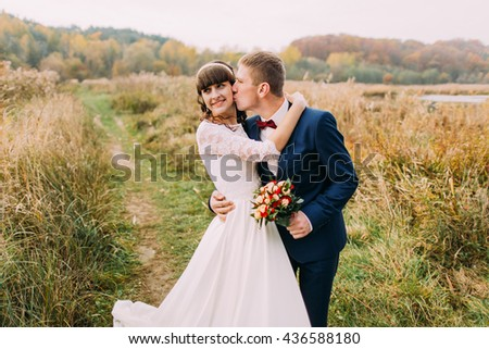Portrait of beautiful newlywed young couple outdoors. Stylish groom kissing his charming bride - stock photo