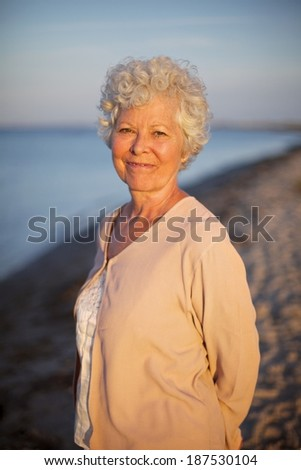 Portrait of beautiful old woman standing alone at the beach. Senior caucasian lady relaxing outdoors - stock photo