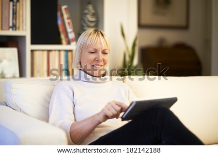 portrait of beautiful old woman using tablet pc and smiling, sitting on sofa at home - stock photo