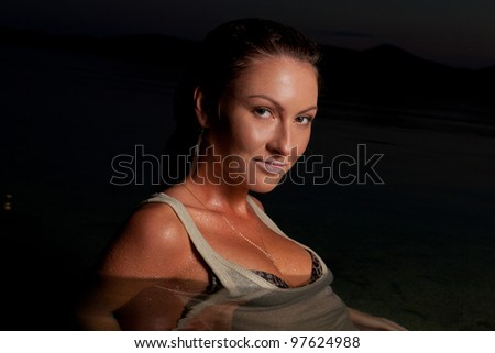 portrait of beautiful passionate brunette standing in the water at the nighttime and looking at the camera