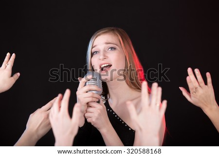 Portrait of beautiful passionate girl singing holding silver vintage microphone, crowd of fan hands on foreground