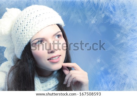 portrait of beautiful pensive brunette over blue winter background