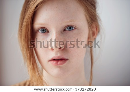 Portrait of beautiful pensive girl with red hair at home. Cute redhead and freckles woman face closeup portrait with healthy skin. - stock photo