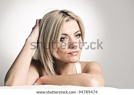 portrait of beautiful peroxide blonde girl on grey - stock photo