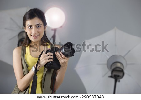 Portrait of beautiful photographer smiling with digital camera in studio - stock photo
