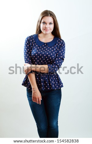 portrait of beautiful plus size brunette young woman posing on gray background - stock photo