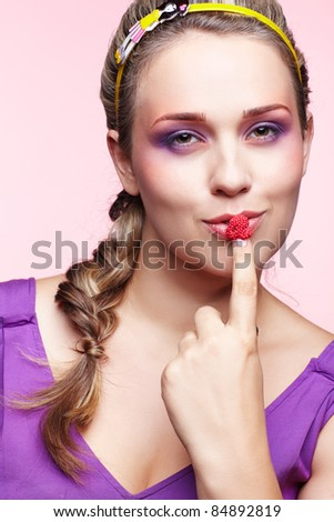 portrait of beautiful plus size curly young blond woman posing on pink with  raspberriy on finger
