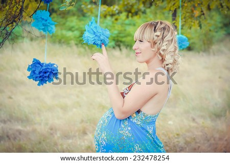 Portrait of beautiful pregnant woman in the park - stock photo