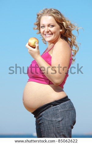 Portrait of beautiful pregnant woman over blue sky